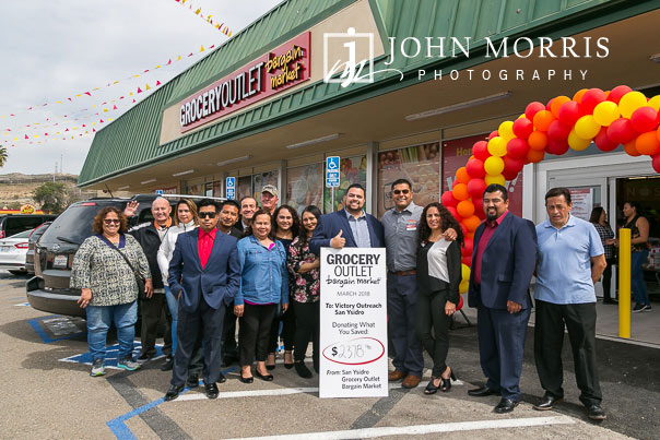 Group photo of owners and donation during a professional event photographed at a grocery store grand opening in San Diego