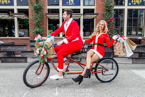 Christmas Fashion Photography Fun. Santa and Mrs Klaus on a tandem bicycle